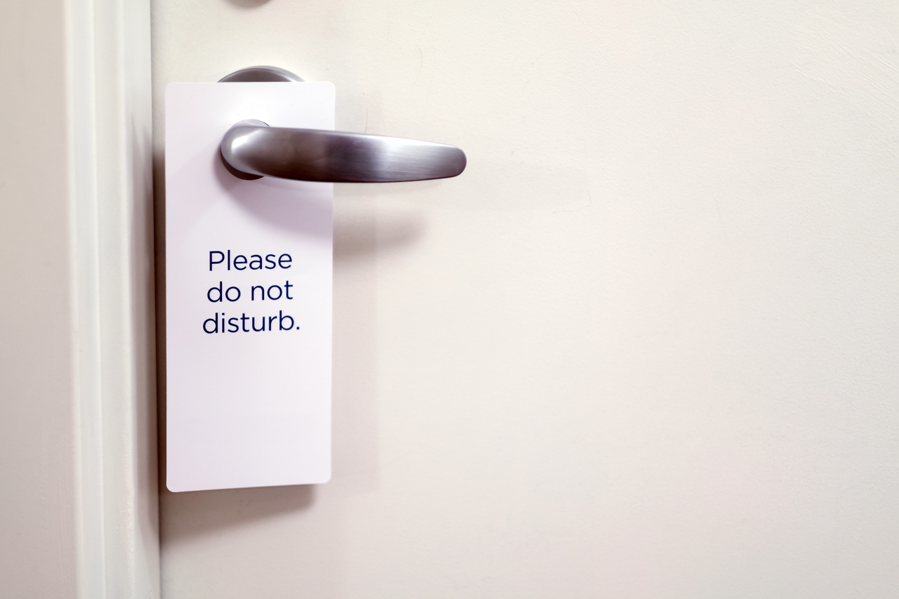 """Close up of a white sign hung on a hotel room door saying """"Please do not disturb."""""""