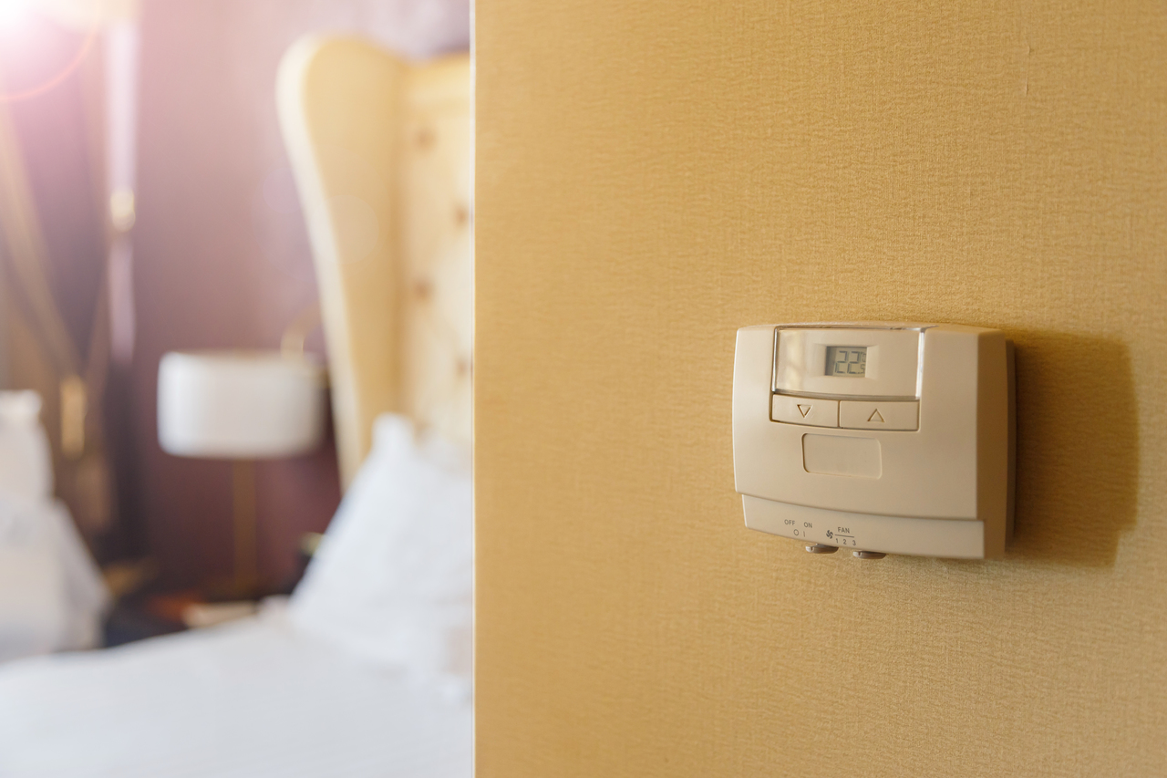 Close-up of a temperature control on a hotel room wall with the room behind it