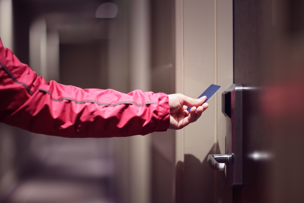 A hand is opening a hotel room door by scanning their key card