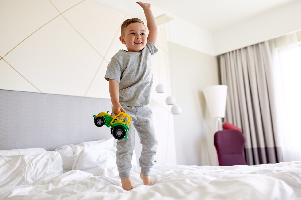 Little boy happily jumping on a hotel room bed