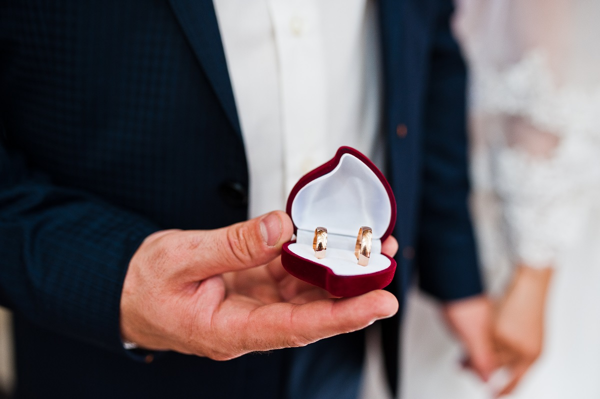 wedding rings at hand of groom on heart shaped box