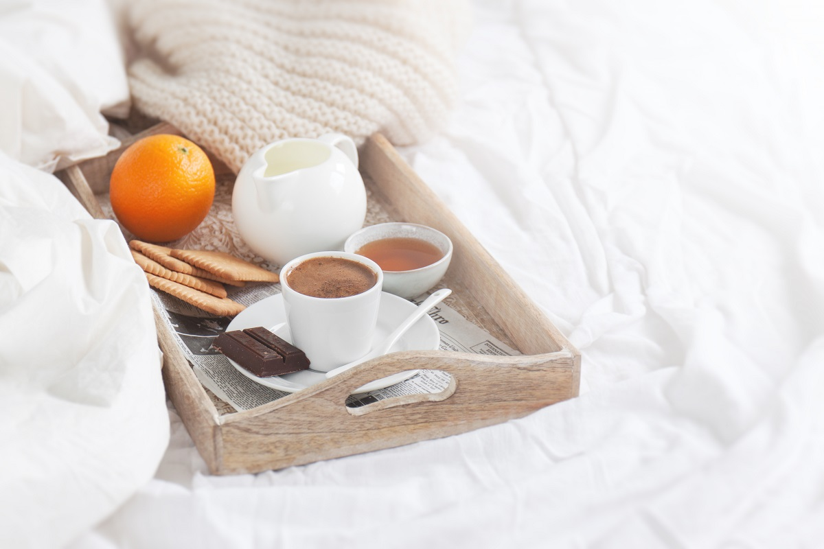 Romantic breakfast on bed with coffee, cookies, orange and choco