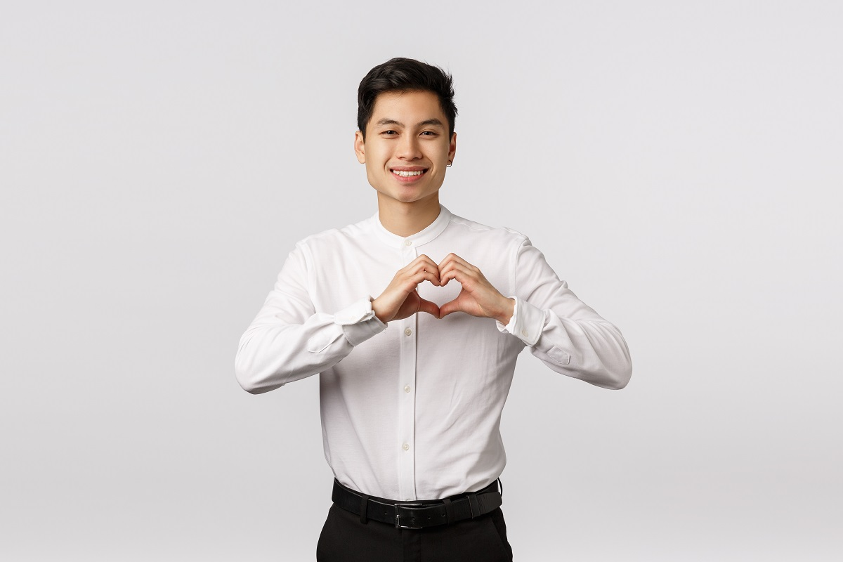 Lovely young asian boyfriend in formal shirt, pants, showing heart sign express love, affection or admiration, smiling camera, invite girlfriend go prom together, standing white background