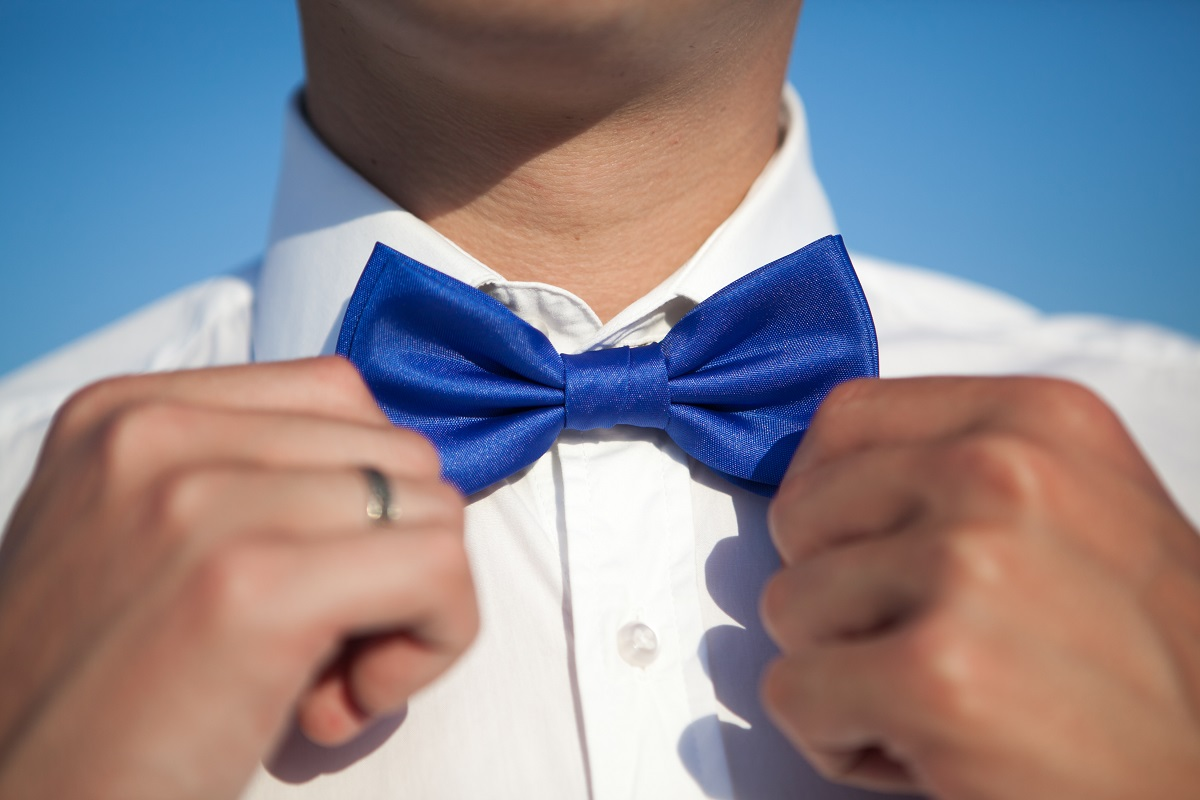 Groom in a white shirt straightens a blue bow tie against a blue sky