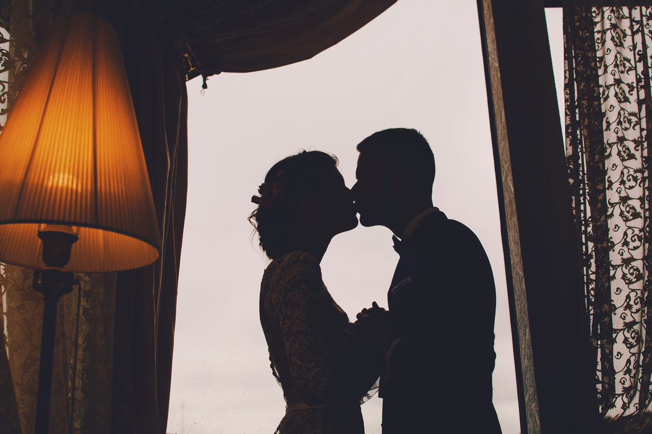 A bride and groom kissing in their hotel suite