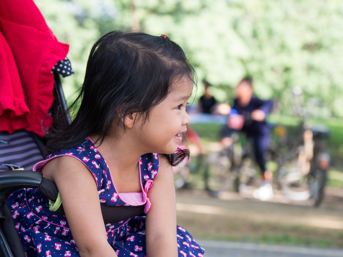 Little asian girl sitting in a stroller at public park. She have be smile.