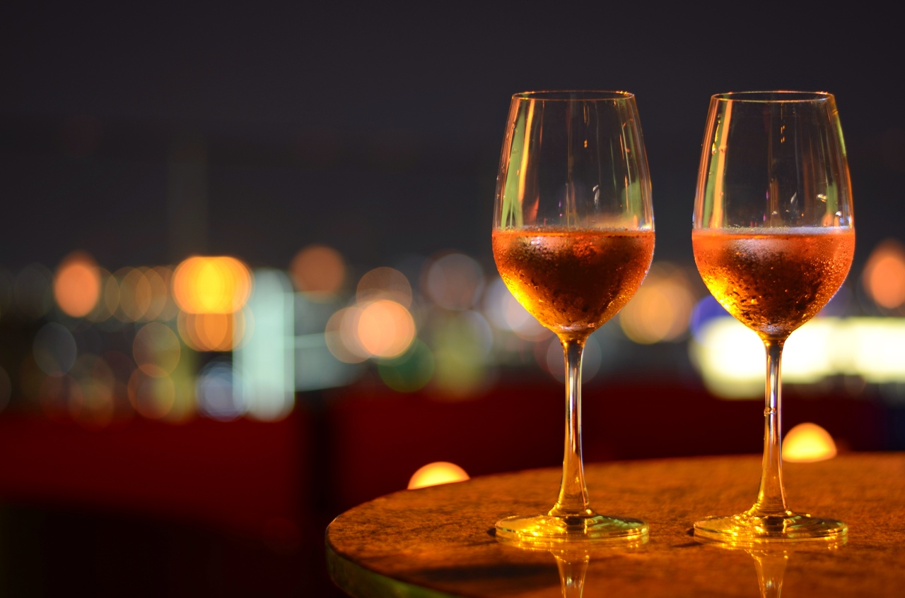Two wine glasses on a rooftop restaurant