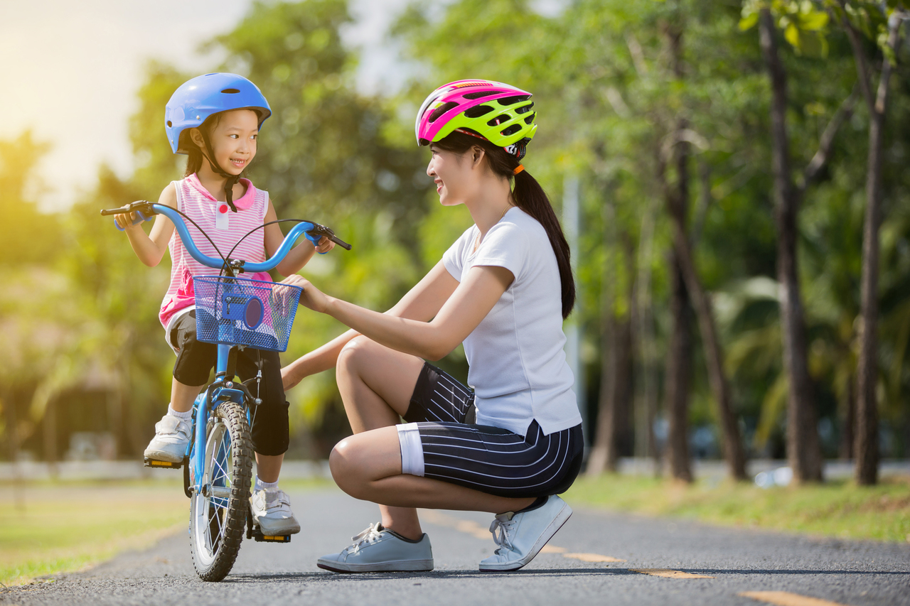 A mother teaching her young daughter how to bike