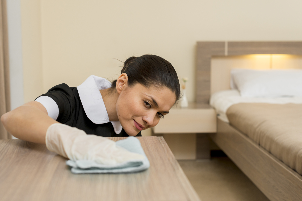 A hotel employee cleaning a drawer